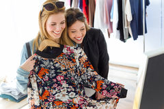 Two beautiful young women shopping in a clothes shop. Royalty Free Stock Image