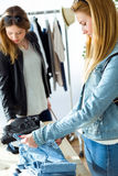 Two beautiful young women shopping in a clothes shop. Stock Images