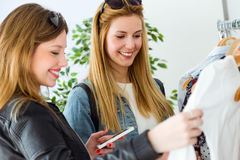 Two beautiful young women shopping in a clothes shop. Stock Image