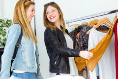 Two beautiful young women shopping in a clothes shop. Stock Photos