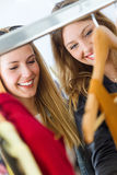 Two beautiful young women shopping in a clothes shop. Royalty Free Stock Photography