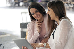 Two beautiful young women sitting on a bench in the city and loo. Two beautiful young smiling women sitting on a bench in the city and looking at the tablet Stock Photo