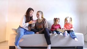 Two young mothers sit with two little daughters on sofa in living room. Two beautiful young women sitting on couch and discussing shopping through online stores stock footage