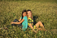 Two beautiful young women sitting in meadow Royalty Free Stock Photos