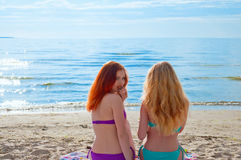 Two beautiful young women sitting on a towel on a beach Royalty Free Stock Image