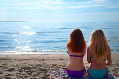 Two beautiful young women sitting on a towel on a beach Royalty Free Stock Photos