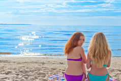 Two beautiful young women sitting on a towel on a beach Stock Photos