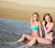 Two beautiful young women sitting in water on a beach. Stock Photography