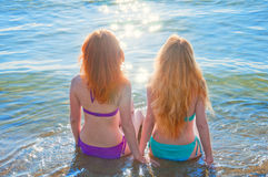 Two beautiful young women sitting in water on a beach. Royalty Free Stock Photo