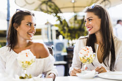 Two beautiful young women smiling and having a fruit salad in a Stock Image