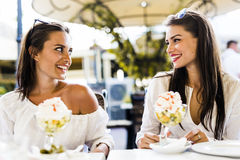 Two beautiful young women smiling and having a fruit salad in a Stock Photo
