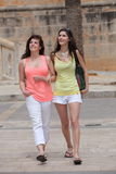 Two beautiful young women strolling in town Royalty Free Stock Image