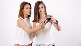 Two beautiful young women taking a selfie and smiling. Slow motion stock video