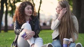 Two beautiful young women talking and drinking coffee outdoors stock footage