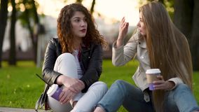 Two beautiful young women talking and drinking coffee outdoors stock video footage