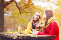Two beautiful young women talking and enjoying on an autumn day Stock Photo