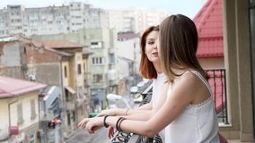 Two beautiful and young women talking and laughing at balcony. Slow motion stock video