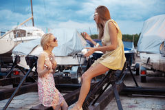 Two beautiful young women are talking on pier Stock Image
