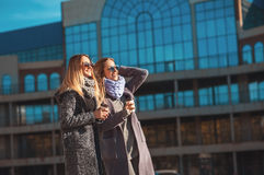 Two beautiful young women talking while walking the street after shopping holding the coffee and smiling. The weather is great tod Royalty Free Stock Photo