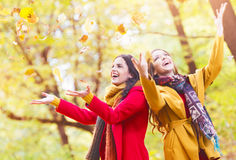 Two beautiful young women throwing leaves in a park Stock Photos