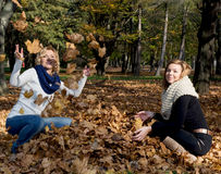 Two beautiful young women throwing yellow leaves Royalty Free Stock Photo