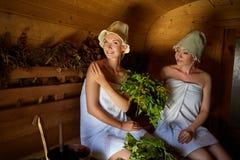 Two girls relaxing in sauna. Two beautiful young women in towels realxing  in wooden sauna e6bd3598f