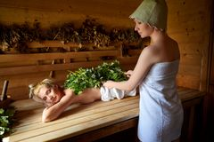 Two girls relaxing in sauna Stock Photos