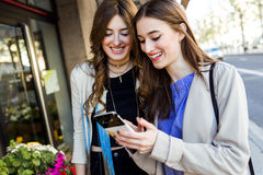 Two beautiful young women using mobile phone in the street. Royalty Free Stock Images