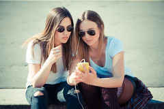 Two beautiful young women using smart phone Royalty Free Stock Image