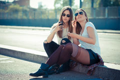 Two beautiful young women using smart phone Stock Images