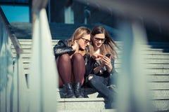 Two beautiful young women using smart phone Stock Image