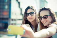 Two beautiful young women using smart phone selfie Royalty Free Stock Photo