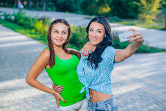 Two beautiful young women using smart phone for Royalty Free Stock Images