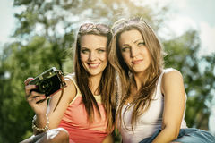 Two beautiful young women using a vintage camera Royalty Free Stock Photos