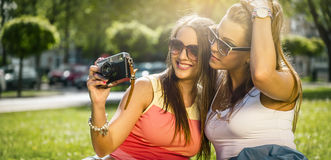 Two beautiful young women using a vintage camera Stock Photo