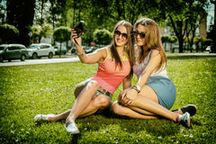 Two beautiful young women using a vintage camera Royalty Free Stock Image