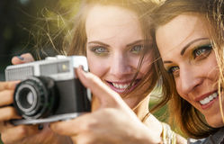 Two beautiful young women using a vintage camera Royalty Free Stock Photo
