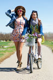 Two beautiful young women with a vintage bike in the field. Stock Photo