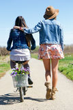Two beautiful young women with a vintage bike in the field. Royalty Free Stock Photo