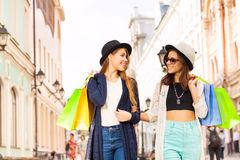 Two beautiful young women walk with shopping bags Royalty Free Stock Photo