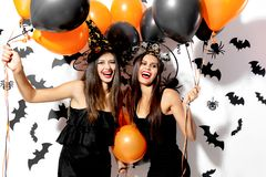 Two beautiful young women in witches hats are with black and orange balloons on a white background with black bats. Halloween stock photography