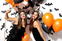 Two beautiful young women in witches hats are with black and orange balloons on a white background with black bats. Halloween royalty free stock photo