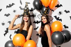 Two beautiful young women in witches hats are with black and orange balloons on a white background with black bats. Halloween royalty free stock photos