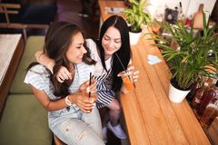 Two beautiful youthful smiling girls with dark hair,dressed in casual outfit,hug each other in a cozy coffee shop. stock photography