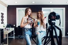 Two beauty bloggers doing make-up and haircare products review filming it on camera for their vlog.  Stock Photography