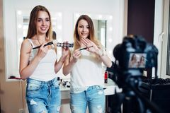 Two beauty bloggers filming a makeup shopping guide demonstrating eyeshadows and brushes against make up mirrors in stock photography