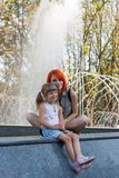 Two beauty girls on fountain Royalty Free Stock Photography