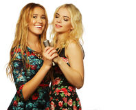 Two beauty girls with a microphone. Life style, happiness, emotional and people concept: two beauty girls with a microphone singing and having fun Royalty Free Stock Photo