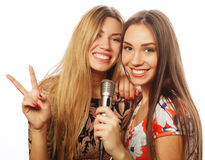 Two beauty girls with a microphone singing and having fun Stock Photos
