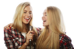 Two beauty girls with a microphone singing and having fun Royalty Free Stock Photos